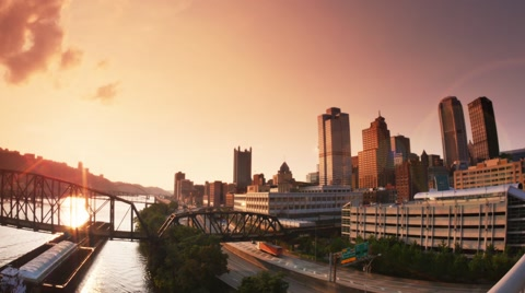4911 An establishing shot of the skyline of Pittsburgh at dusk as a coal barge passes by.