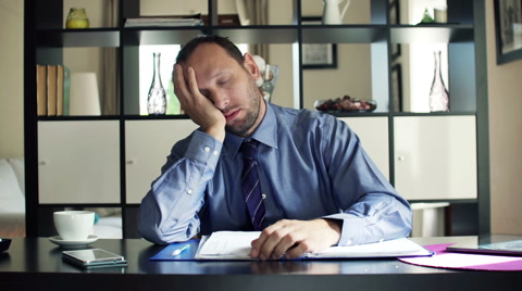 Tired businessman yawning and sleeping sitting by desk at home HD