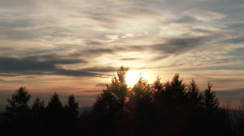 Colorful sunset clouds time lapse with sun setting behind forest trees in Portland, Oregon.