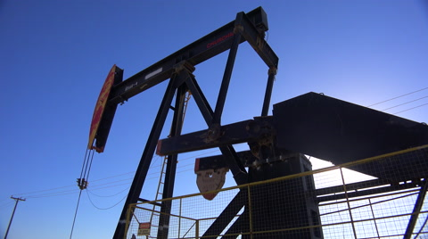 Low angle of oil derrick pumping against blue sky.