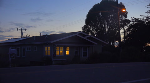 A 1940's style house with the lights on at night.
