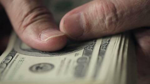 Close up of hands of an old man counting hundred dollar bills at a table. Slow motion