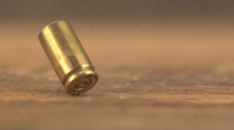 Bullet cases from a 9mm automatic pistol hitting the floor after firing with smoke from casings. Slow-motion, 1/8th natural speed.