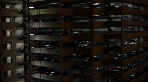 White car drives through enormous, multi-level city parking garage, lit at night. 4K UHD 3840x2160