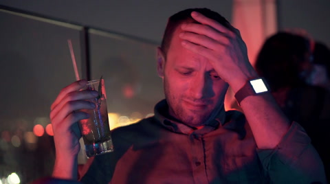 Sad, unhappy man drinking cocktail sitting on terrace in cafe at night  HD