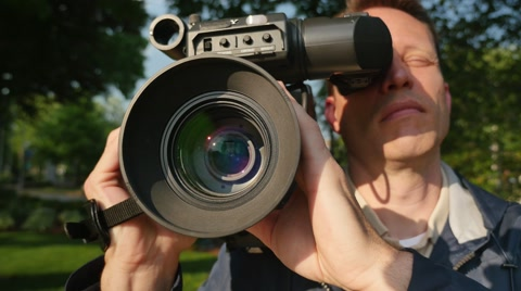 5893 A close up shot of a cameraman focusing a shoulder-mounted camera.