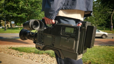 5895 A low angle shot of a cameraman carrying his video camera to a production.