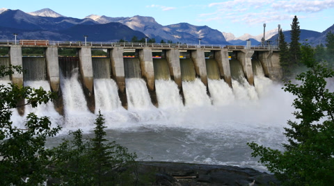 Wide shot of the Kananaskis hydroelectric power dam on the Bow River with mountain background, Alberta, Canada