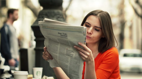 Young woman reading newspaper while sitting in cafe in city  HD