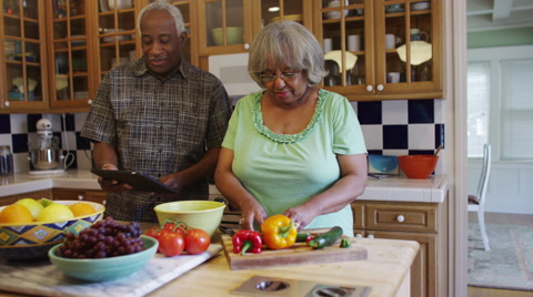 Senior black couple cooking together in kitchen