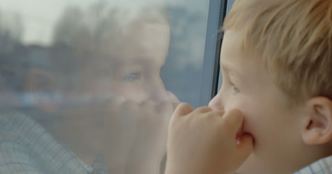 Close-up shot of a little child in the train. Boy looking out the window with hands close to face and reflection in the glass