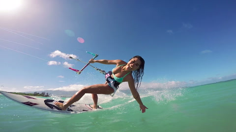 Slow motion shot of extreme asian woman kite surfing in ocean on summer day.