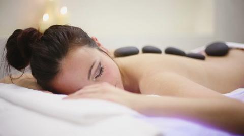 Woman in spa salon with hot stones. Slider camera movement
