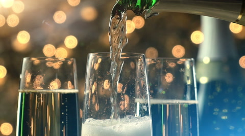 A slow motion pour of champagne into a champagne glasses with bubbles and foam pouring over the glass.  The background is Christmas lights and warm and cool toned flares.