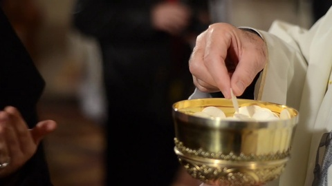A priest is giving a Sacrament of Bread to his pasque. Catholic priest places communion bread in the mouth of worshippers. Eucharist. Christmas Midnight mass in a Catholic Church. Sacramental bread. Priest in the church.