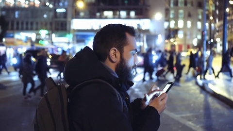 A young man is commuting to work while browsing his cellphone on a busy urban street at night.