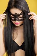 portrait of beautiful sensual woman in black lace mask on the yellow background. sexy girl in venetian mask