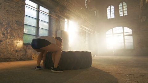 Fit Athletic Woman Lifts Tire as Part of Her Cross Fitness/ Bodybuilding Training.  Shot on RED EPIC-W 8K Helium Cinema Camera.