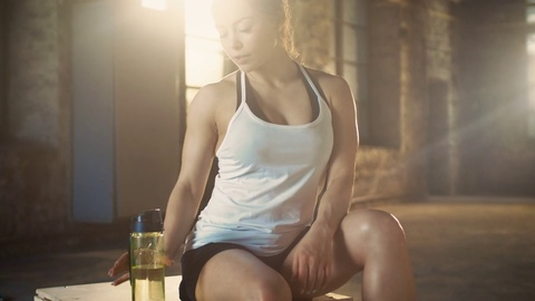Strong Athletic Woman Drinks From a Water Bottle After Exhausting Cross Fitness Bodybuilding Training at Her Favourite Gym. Shot on RED EPIC-W 8K Helium Cinema Camera.