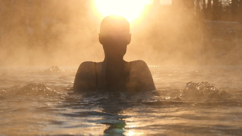 Geothermal spa. Woman relaxing in hot spring pool outdoors. Girl enjoying bathing in a blue water lagoon tourist attraction at sunset. Slow motion