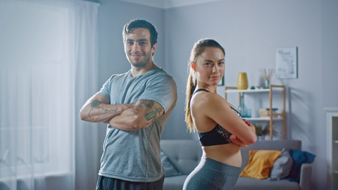 Muscular Athletic Man and Beautiful Fitness Woman in Workout Clothes are Confidentally Posing in Their Bright and Spacious Apartment with Minimalistic Interior. Shot on RED EPIC-W 8K Helium Cinema Camera.