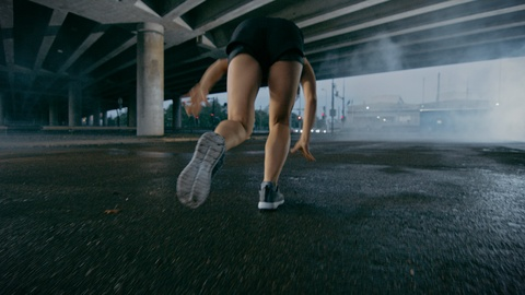 Beautiful Strong Fitness Girl in Black Athletic Top and Shorts Starts Sprinting. She is Running in an Urban Environment Under a Bridge with Cars in the Background. Shot on RED EPIC-W 8K Helium Cinema Camera.