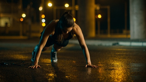 Beautiful Energetic Fitness Girl in Black Athletic Top and Shorts is Doing Push Up Exercises. She is Doing a Workout in an Evening Wet Urban Environment Under a Bridge with Cars in the Background. Shot on RED EPIC-W 8K Helium Cinema Camera.