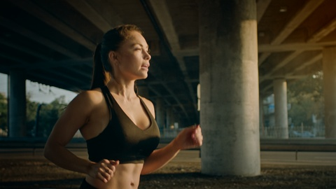 Slow Motion Close Up Shot of a Beautiful Fitness Girl in Black Athletic Top Jogging in a Sunny Street. She is Running in an Urban Environment Under a Bridge with Cars in the Background. Shot on RED EPIC-W 8K Helium Cinema Camera.