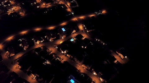 An aerial over a suburban neighborhood at night, as disaster strikes and the city loses power.  ---  CITIZENP5BRIEF