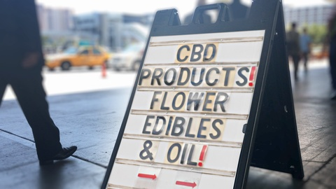 11832 A daytime view of a sign outside of a CBD products store. Traffic and pedestrians pass by in the background.