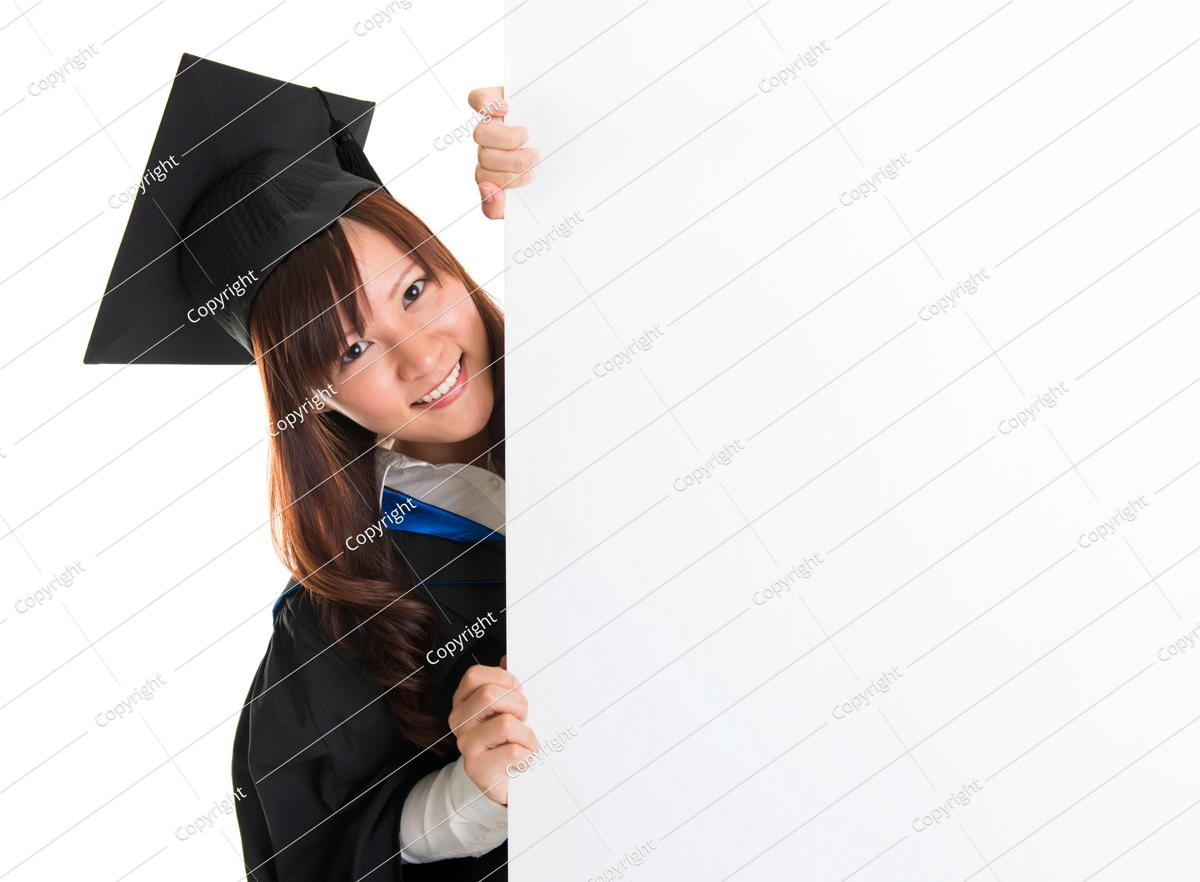 portrait of smiling asian female student in graduate gown peeking, hiding behind a white card, isolated on white background