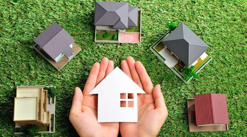 A imagem mostra miniaturas de casas sobre grama.