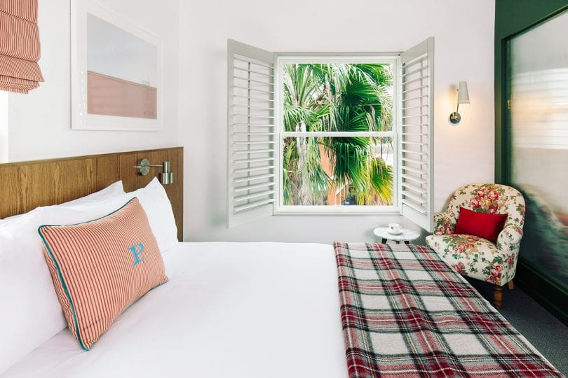 Culver City - room detail - bed, headboard,floral chair, window looking out to palm tree