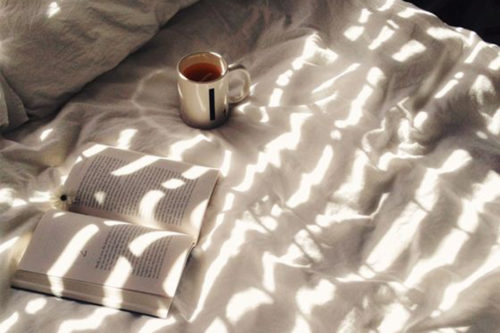 book and cup of coffee on bed with sunlight pattern