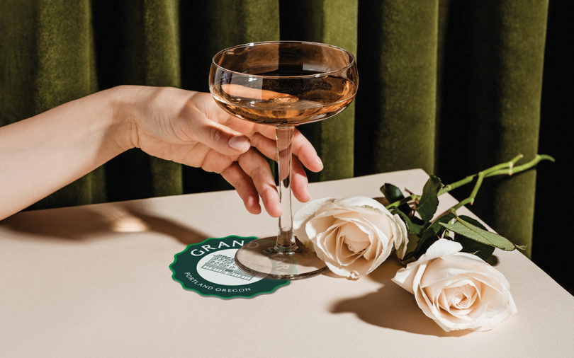 x reaching for champagne glass roses on table