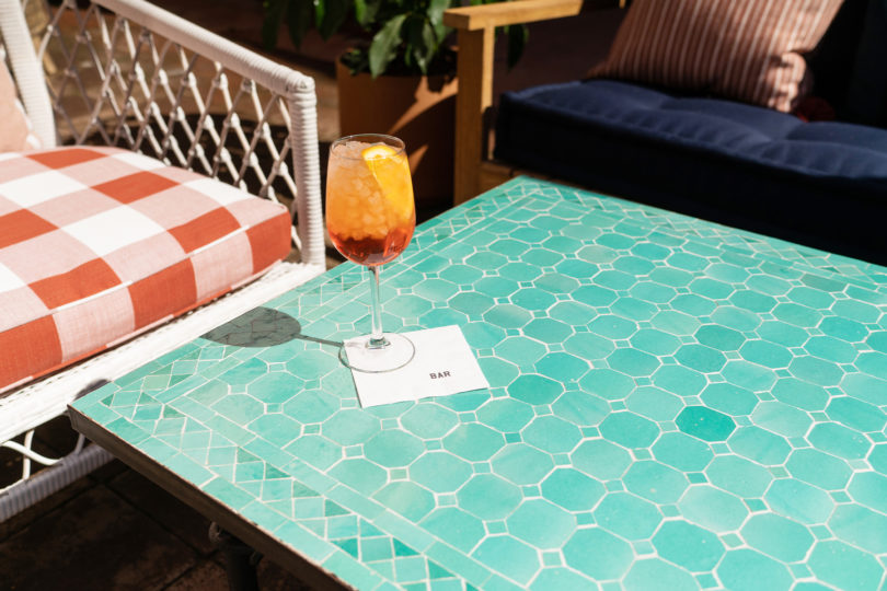 orange cocjtail on seagreen tiled table and chairs