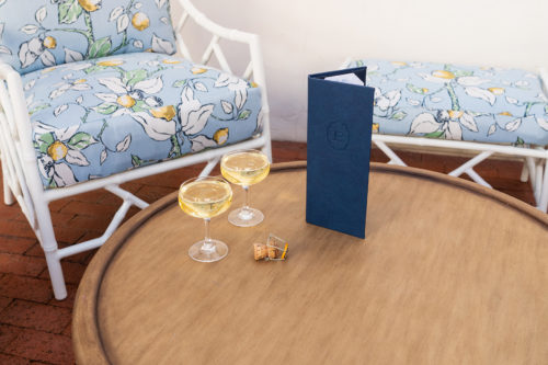 champagne and menu on wood table with plush chairs