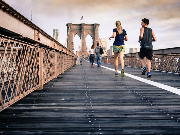couple running across brooklyn bridge