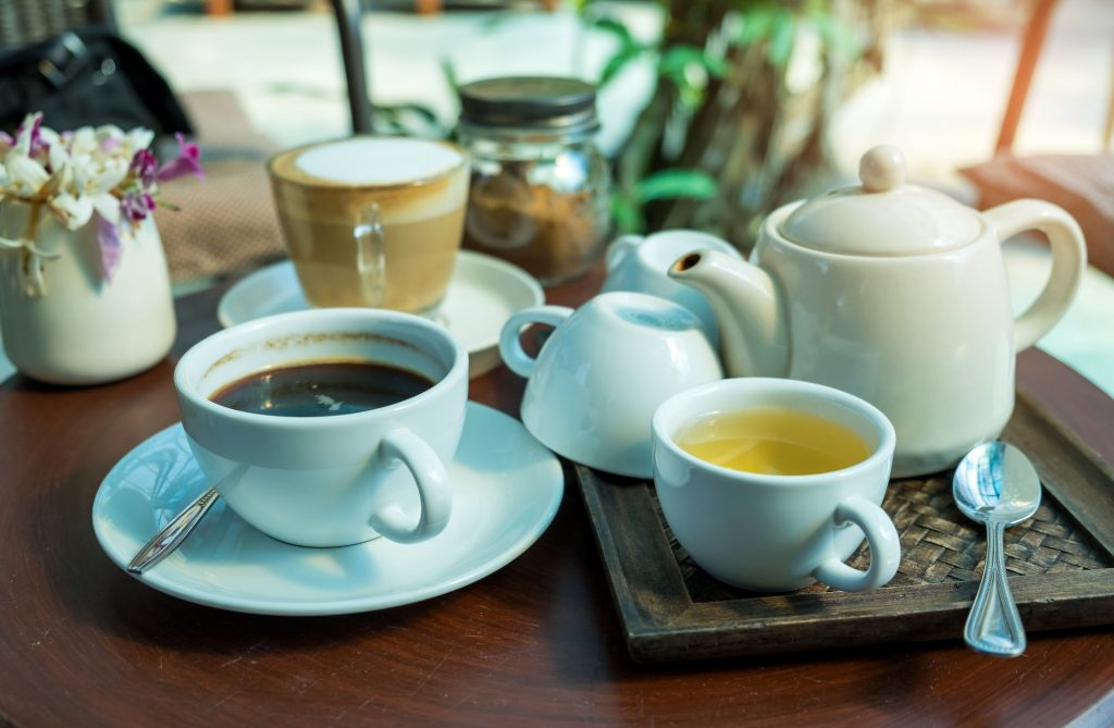 Coffee and Tea on wooden table.Glass tea placed in a wooden tray.