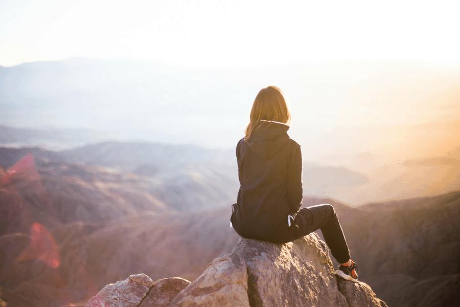 woman sitting on a mountain accomplished goal