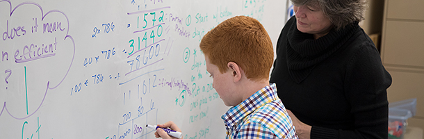student and teacher at white board