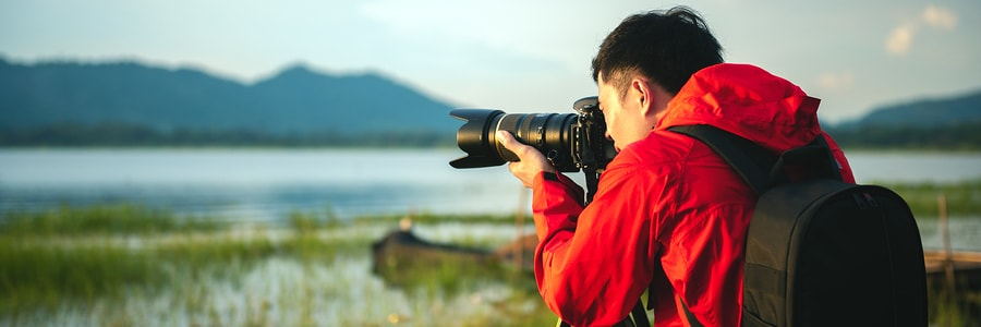 man in bright red coat taking photos of nature for his photography business