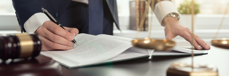 lawyer at desk with pen and notebook working to help a startup
