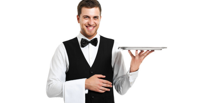 A photo of a waiter in uniform smiling and holding a tray prepared to work