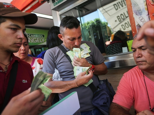 Venezuela's currency now worth so little shopkeepers weigh vast piles of notes instead of counting t