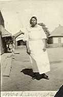 Image of Collection of historic photographs - Woman (Mrs. Devereaux) standing outside of housing structures.
