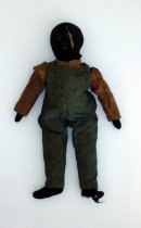 Image of Black rag doll wearing overalls and red print shirt.