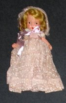 Image of Bridesmaid: Family Series #87 - Young blonde girl wears mauve-colored dress with flowers and pink ribbon attached below PR hand, silver slippers and mauve-colored bonnet with flowers in her hair. Jointed arms and legs.