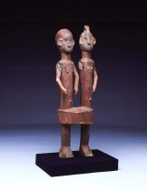 Image of Male/female pair, undetermined group. Two figures share on pair of over-sized legs. Simplistic, elongated bodily features reminiscent of Senufo rhythm pounders from the Ivory Coast.