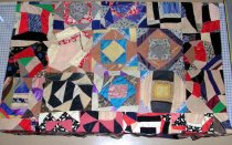 Image of Crazy quilt - Quilt with no batting or backing material; colorful geometric shapes made with scraps of material, some diamond shapes.